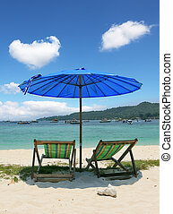 A chaise lounges and dark blue beach umbrella - A...