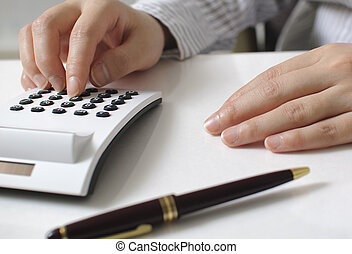 Businesswoman calculating expenses in the office