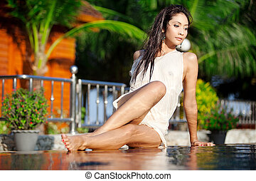 Beautiful Thai woman - Sexy Asian woman lays on edge of pool...