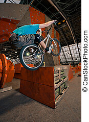 Cyclist standing on box on back wheel - Cyclist standing on...