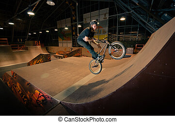 Biker doing bar spin trick in wooden ramp