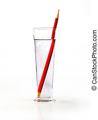 Tall glass of water, with a red pensil inside.