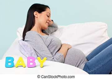 Pregnant woman BABY word in front.
