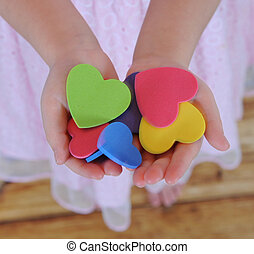 closeup of childs hands holding colorful hearts - extreme...