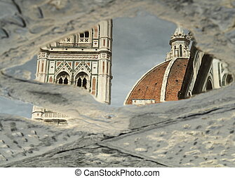 reflection of famous florentine cathedral in puddle and...