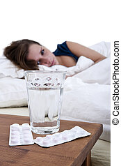 Self medication - Sick woman in bed, looking at a glass of...