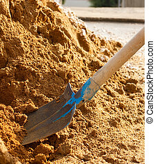 Spade and sand - Closeup of a shovel digging into pile of...