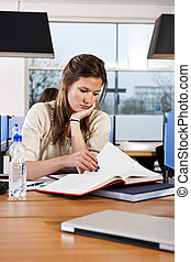 Student - Pretty student, concentrating on a text book,...