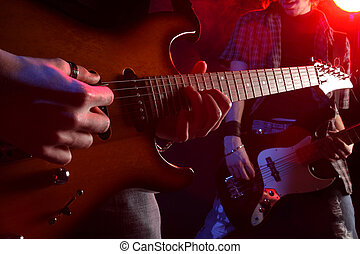 rock musicians playing at a live concert, similar photo on...