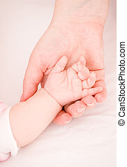 Tenderness and care of the parent of the kid - parental hand...