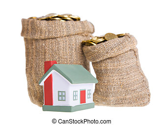 Toy small house and bags with money. The concept of purchase...