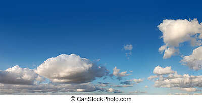 Blue sky with several cumulus white clouds.