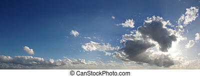 Blue sky with several cumulus clouds in background.