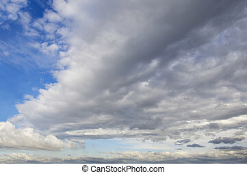 Blue sky with cumulus clouds in background and a large cloud front.
