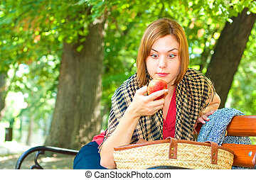 I will eat you - Red-haired woman sitting on a bench and...