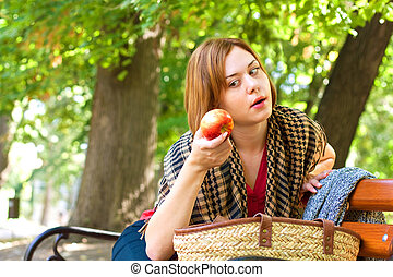 I will eat you - Red-haired woman sitting on bench and...