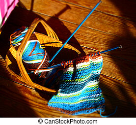 Knitting Basket - A knitting basket with colorful yarn, and...