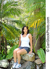 Tropical rockery - Attractive brunette lady sitting on a...