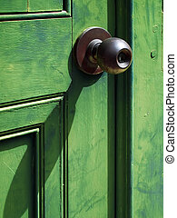 Old iron doorknob on Green wood door