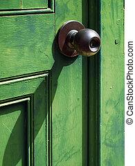 Old iron doorknob on Green wood door