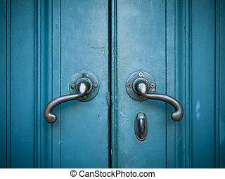 Door handles with an old double door painted with blue