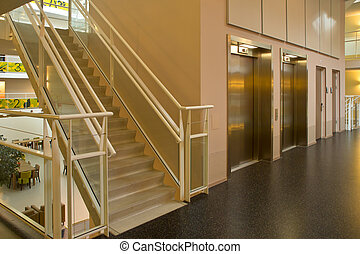elevator staircase in a modern building - An elevator and...