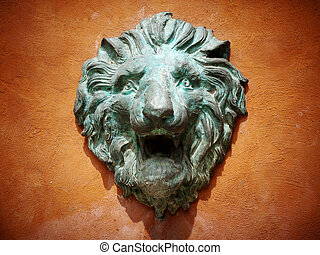 Cast green metal lion head on the orange wall
