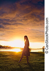 Girl in Sunset - beautiful girl standing on river shore in...