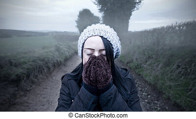 woman cold standing on country lane