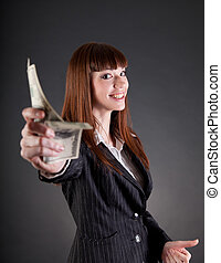 Smiling business woman with dollars offering credit, studio...