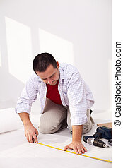 Casual man laying isolation foam beneat flooring