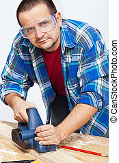 Carpenter or joiner working with electric planer
