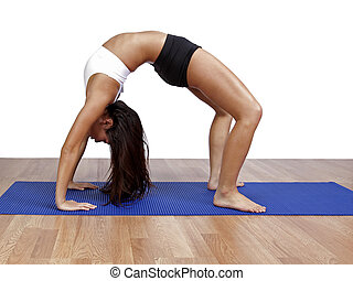 Young woman arching in gym - Young woman arching backwards...