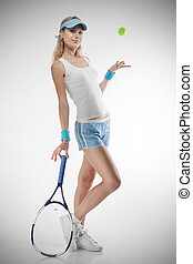 Portrait of young smiling woman with tennis racket and ball...