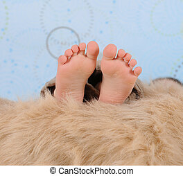 extreme close-up of child's feet over a furry blanket