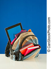 Backpack with colorful books and tablet PC on the blue...