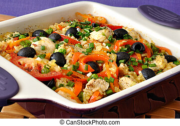 Baked rice with chicken, vegetables and olives in a saucepan
