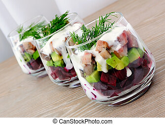 Appetizer in a glass of beet and herring with avocado -...