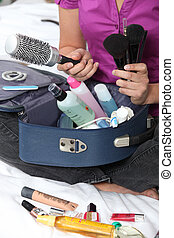 Woman packing her make-up bag