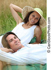 40 years old man and woman relaxing and lying down in a...