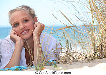 Attractive blond woman laid on the beach