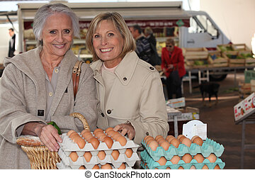 Mother and daughter buying eggs at a market