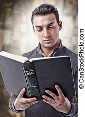 Reading Holy Bible - Portrait of a young man reading the...