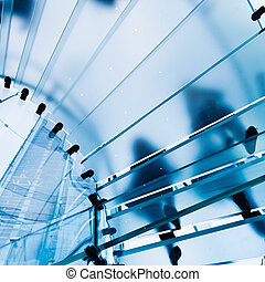 Modern Glass Staircase Silhouette of walking People in...
