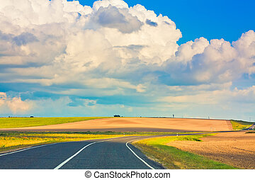 Empty curved road, blue sky - Open road highway with green...