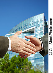 Business deal - Handshake in the city, selective focus