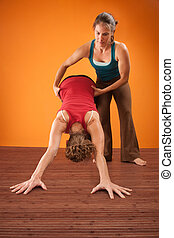Help With Yoga - Woman assists her partner in a yogasana...