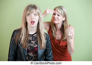 Frustrated Mom - Frustrated mother behind angry daughter in...