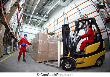 two workers reloading pallets - goods delivery in...