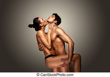 Passionate Naked Couple standing with womans raised leg...